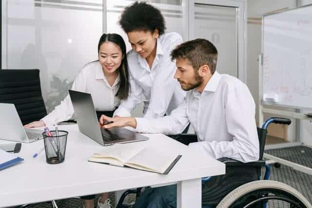Grupo de advogados conversam olhando para o computador. Todos usam roupas sociais e parecem estar num escritório.